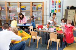 Two toddler teachers assisting play centers in classroom