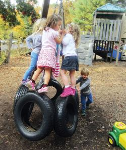 Four children playing on tire swing