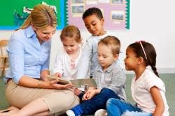 Teacher with a group of diverse young children on the floor