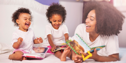 Mother reading and laughing with her two young daughters