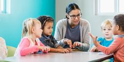 Preschool teacher guides students at table