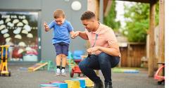 Teacher helps a boy jump over buckets on a playground
