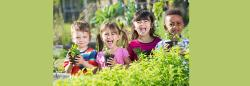 Group of diverse children holding plants outside