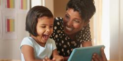 Teacher and preschooler looking at a tablet