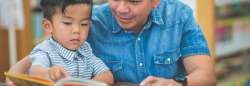 Male teacher and preschool student reading a book