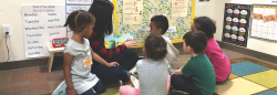 Teacher reading book to diverse students