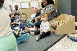 Toddlers in a classroom with their teachers, playing on the floor.