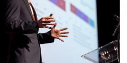 A person speaking on a stage near a podium