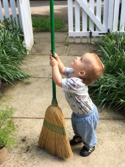 Toddler holding a broom outside