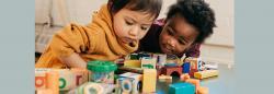 Two toddler girls playing with blocks