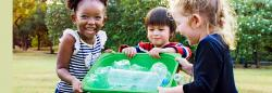 Diverse preschoolers holding a recycling bin with plastic bottles