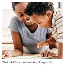 Mother and toddler song talking and pointing to a book