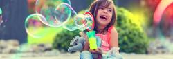 Child playing with bubble machine