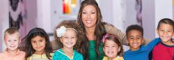 Teacher and preschoolers smiling in a classroom