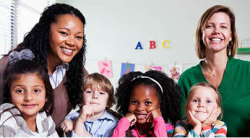 Young children and teachers smiling in the classroom