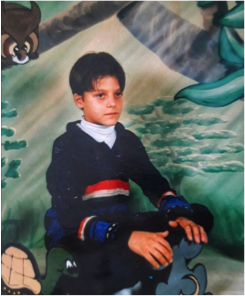 A picture of the author in 3rd grade.  Shows a boy sitting in front of a painted background.