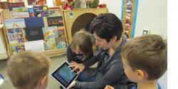Teacher showing young children iPad
