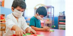 Two children playing in a classroom wearing protective masks.