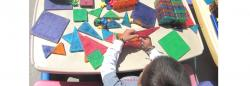 Child stacking brightly colored shapes