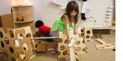 young girl putting together a 3D block puzzles using blocks