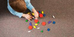 A preschooler plays with geometric shapes on a carpet