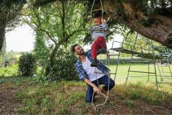 A father plays outside with their child on a rope ladder