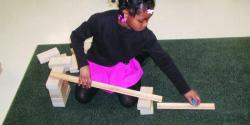 A young girl plays with blocks to make a ramp