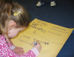 Child writing on poster