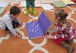 Two children creating a project with cardboard box