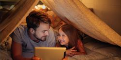father and daughter playing on a tablet under a homemade fort.