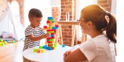 A young boy plays with some blocks while a teacher observes.