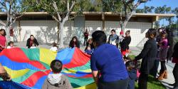A group of children and their parents play with a rainbow-colored parachute.