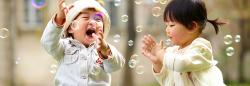 Two children playing with bubbles