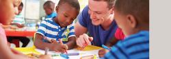 Teacher helping three preschool students with coloring