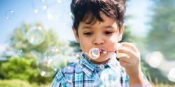 Preschool aged boy blowing bubbles outside