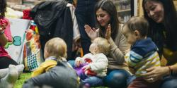 Infants and their parents sit in a circle clapping and singing together