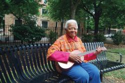 Ella Jenkins sitting on a bench with a guitar in her hands