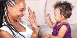 Toddler playing hand game with mother