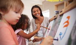 An educator painting with her two students.