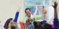 Teacher raising hand with students