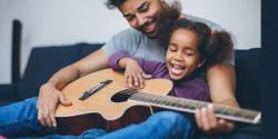 Father and daughter playing guitar on couch