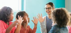 Teacher and three preschool students with hands up