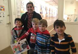 Teacher and students smiling with artwork