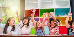 Diverse group of children in a classroom raising their hands in the air!
