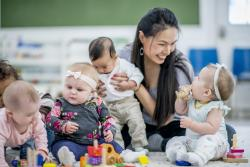 Teacher in a classroom with babies sitting on the floor with blocks