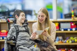Teacher in a classroom with a young boy in a wheeler reading a card