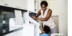 Mother and young son in a laundry room looking at clothing
