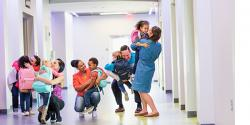 5 parents, each hugging their child in a school hallway