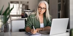 Woman at a laptop taking notes