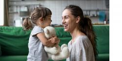 Mother and and a little girl holding a teddy bear